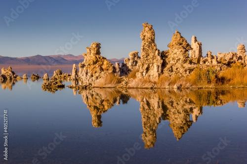 Fotografía Reflection Of Rocks In Lake Against Clear Blue Sky