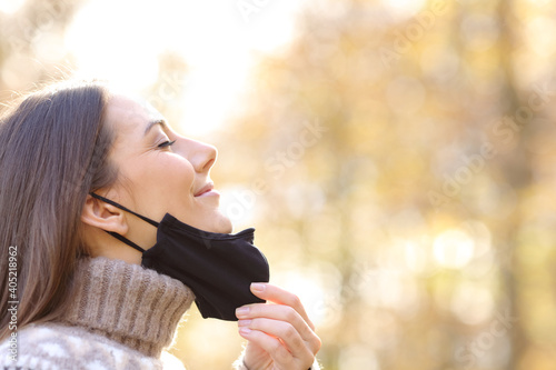 Obraz Satisfied woman taking off mask breathing in a park - fototapety do salonu