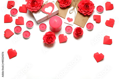 Several pink wax candles, gifts, 3D handmade red paper roses and hearts on white background. Love, Valentine's, mother's, women's day, relations, romantic, wedding concept