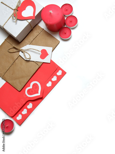 Gifts and pink candles, tied with twine with bows and labels with red paper hearts, love letter in red envelope with hearts white background isolated. Love, Valentine's, relations, romantic concept
