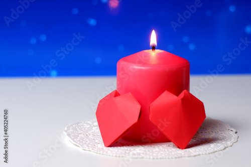 Couple of 3D red paper hearts, burning pink candle on white openwork paper napkin, blue bokeh snow background closeup view selective focus. Love, Valentine's, women's day, relations, romantic concept