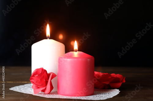 White and pink burning aromatic candles, roses, gift on white openwork paper napkin on wooden table, selective focus. Love, Valentine's, women's day, romantic, dating, rendezvous concept
