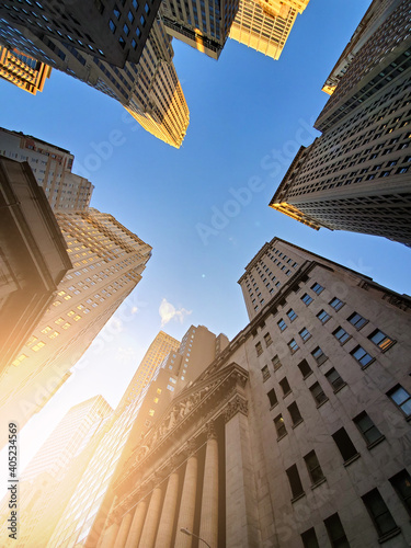 Buildings of Wall Street towering overhead against a blue sky background in the historic financial district of New York City
