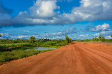 Sunset View Of A Typical Red Soils Unpaved Rough Countryside Road In Guinea, West Africa.