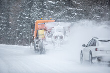 Poor Road Visibility Of A Car Driving Right Behind A Snow Plow During Winter Road Maintenance