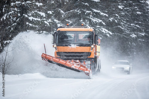 Snowplow clearing road from snow in the forest with traffic lining up behind the truck