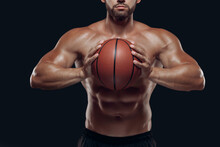 Close Up Of A Basketball Held By A Muscular Player With Naked Torso Ready To Throw, Isolated On Black Background