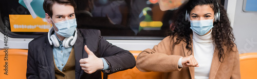 Obraz interracial couple in medical masks bumping elbows in subway, banner - fototapety do salonu