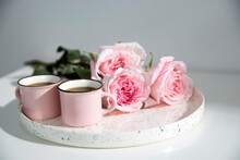 Two Small Pink Cappuccino Cups With Three Pink Roses On A Tray On A Coffee Table