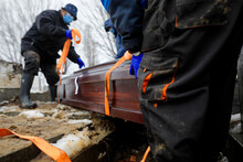 Shallow Depth Of Field (selective Focus) With Undertakers Burying A Coffin Containing A Victim Of SARS-CoV-2 On A Cold Snowy Winter Day.