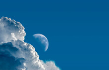Daytime Moon In The Blue Sky With Clouds