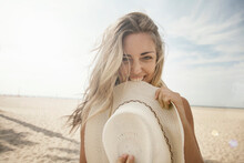 Playful Young Woman With Blond Hair Biting Hat At Beach On Sunny Day