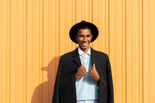 Cheerful Young Man Holding Blazer Against Yellow Corrugated Iron On Sunny Day