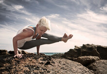 Blond Woman Practicing Astavakrasana On Rock Formation At Beach Against Sky