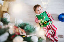 Baby Boy In Elf Costume Playing With String Light While Lying On Floor At Home During Christmas