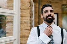 Smiling Handsome Groom Adjusting Necktie At Home