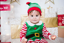 Cute Baby Boy In Elf Costume Playing While Sitting At Home During Christmas
