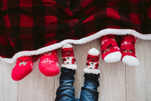 Parents And Baby Boy Wearing Christmas Socks At Home During Christmas