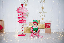 Baby Boy In Elf Costume Playing With Lights While Sitting By Welcome Sign At Home During Christmas
