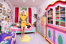 Young Woman With Hand Raised Sticking Out Tongue Standing In Flashy Bedroom