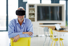 Smiling Businessman Using Virtual Reality Headset While Leaning On Chair At Home