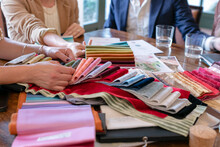 Couple Choosing Fabrics With Event Planner In Her Studio
