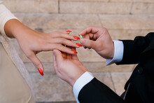 Groom Placing Ring On Bride During Wedding Day