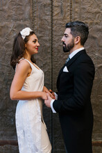 Couple Holding Hands By Door Of Church On Wedding Day