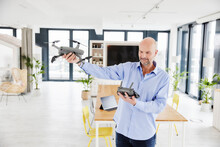 Businessman Examining Quadcopter While Standing At Home