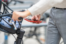 Man Unlocking Bicycle With Mobile Phone While Standing In City