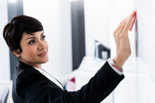 Portrait Of Businesswoman Placing Adhesive Note On Office Whiteboard