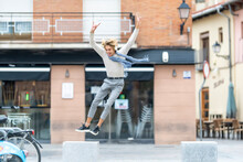 Carefree Young Man Jumping From Bench With Hands Raised In City