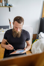 Beard Man Sitting With Color Palette In Living Room
