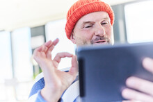 Mature Man Showing OK Hand Sign While Talking To Video Call On Digital Tablet At Home