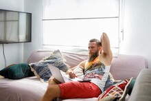 Bearded Man Using Laptop While Sitting On Sofa In Living Room
