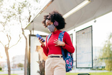 Young Woman Wearing Headphones And Protective Face Mask Using Smart Phone While Standing At Bus Stop