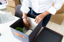 Hands OfÔøΩbusinesswoman Packing Boxes Before Office Relocation