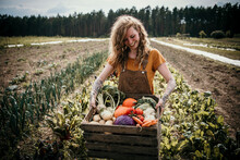 Smiling Farm Worker Carrying Vegetable Box While Standing At Farm