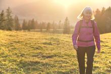 Portrait Of Senior Hiker Walking Across Alpine Meadow At Sunset