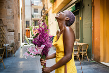 Cheerful Woman With Flowers Standing By Sidewalk Cafe In City