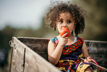 Girl Looking While Eating Tomato Sitting In Truck