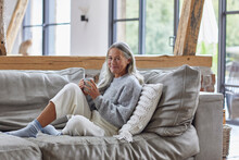 Smiling Mature Woman Holding Coffee Cup While Sitting On Sofa At Home
