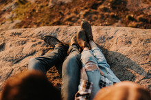 Legs Of Young Couple Sitting Together On Rocky Surface