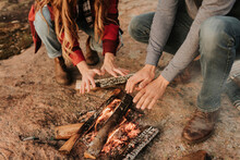 Young Couple Warming Hands By Campfire