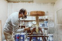 Male Carpenter Using Paint Spray Gun On Table While Working At Workshop