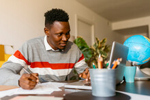 Smiling Male Entrepreneur Looking At Laptop While Writing On Paper In Home Office
