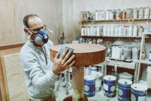 Carpenter Wearing Protective Face Mask Rubbing Table With Sand Paper While Standing At Workshop