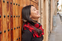 Thoughtful Woman Smiling While Leaning On Wooden Door