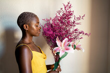 Woman In Yellow Dress Smelling Flowers By White Wall At Home
