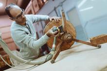 Craftsman Using Sander On Table While Standing At Workshop